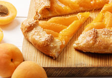 Domowej roboty biskwitowy kulebiak z brzoskwiniami na białym drewnianym stole Zdjęcia Stock