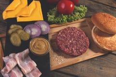 Domowej roboty cheeseburger świezi składniki sery, babeczka, solony ogórek, wołowina paszteciki, bekon zdjęcia stock