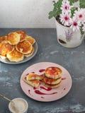 Domowej roboty cheesecakes na ceramicznych talerzach, białym lody pucharze z łyżką, zmianową i deserową, horyzontalny wizer obraz stock