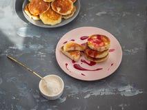 Domowej roboty cheesecakes na ceramicznych talerzach, białym lody pucharze z przesunięciem i deserowej łyżce, obrazy royalty free