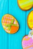 Domowej roboty ciastka z lodowaceniem w formie jajka dla wielkanocy Wyśmienicie Wielkanocni ciastka na błękitnym tle Barwiony gla Obrazy Stock
