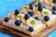 Domowej roboty crispbread grzanka z serem, bananem i jagodami na drewnianej desce chałupy, Chałupa sera kanapki pomysł zbliżenie Obrazy Stock
