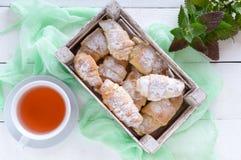 Domowej roboty croissants z dżemem, dekorującym z sproszkowanym cukierem i filiżanką ranek herbata Zdjęcie Royalty Free