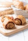 Domowej roboty cynamonowej rolki chleb i piekarnia na białym drewnie Fotografia Stock
