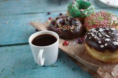 domowej roboty donuts na papierowej i czarnej kawie w białej filiżance Zdjęcia Royalty Free