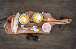 Domowej roboty dyniowa kremowa polewka w emalia kubkach z ziele i świeżego chleba plasterki na oliwnej porci wsiadamy nad nieocio Obraz Stock