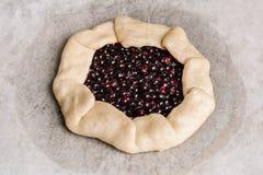 Domowej roboty galette kulebiak z rodzynkami, czarnymi jagodami i malinkami na drewnianym tle czerwonymi i czarnymi, zdjęcia stock