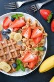 Domowej roboty gofry słuzyć z truskawkami, czarnymi jagodami i bananem, Fotografia Royalty Free