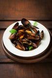 Domowej roboty gotujący mussels z czosnkiem, pomidorowym kumberlandem, włoskimi ziele, białym winem i świeżym basilem w talerzu, zdjęcia royalty free