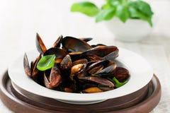 Domowej roboty gotujący mussels z czosnkiem, pomidorowym kumberlandem, włoskimi ziele, białym winem i świeżym basilem w talerzu, zdjęcia stock