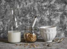 Domowej roboty granola, dojna butelka i ceramiczny puchar na lekkim tle, Zdjęcia Stock