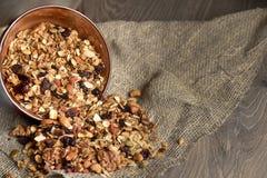 Domowej roboty granola rozlewa od pucharu na drewnianym stole Obraz Stock