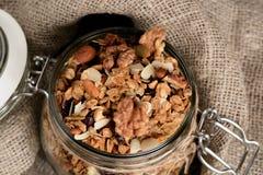 Domowej roboty granola w otwartym szklanym słoju na nieociosanym drewnianym tle obraz royalty free