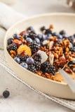 Domowej roboty granola z dokrętkami i koksem z jagodami wewnątrz i mlekiem obraz stock