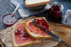 Domowej roboty grzanka z truskawkowym dżemem na drewnianej desce, wyśmienicie śniadanie Zdjęcie Stock
