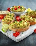 Domowej roboty Guacamole grzanka z chili pieprzem, pietruszka na białej drewnianej desce Zdjęcia Royalty Free