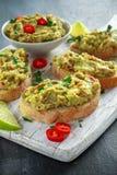 Domowej roboty Guacamole grzanka z chili pieprzem, pietruszka na białej drewnianej desce Zdjęcia Stock