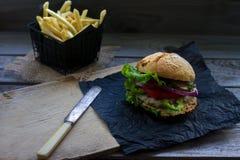 Domowej roboty hamburger z świeżymi pomidorami, sałatą, cebulami i smażyć grulami na nieociosanej drewnianej desce, Fast food, ni obrazy royalty free