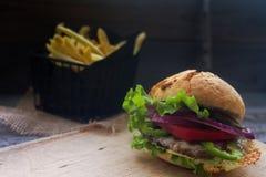 Domowej roboty hamburger z świeżymi pomidorami, sałatą, cebulami i smażyć grulami na nieociosanej drewnianej desce, Fast food, ni obraz stock