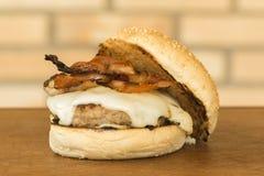 Domowej roboty hamburger z serem, bekon i babeczka na stronie nad drewnianym tłem tnącej deski i cegły obrazy royalty free