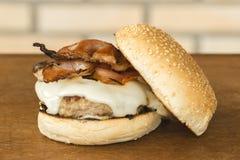 Domowej roboty hamburger z serem, bekon i babeczka na stronie nad drewnianym tłem tnącej deski i cegły zdjęcia stock