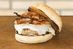 Domowej roboty hamburger z serem i bekonem nad drewnianym tłem tnącej deski i cegły zdjęcie royalty free