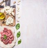 Domowej roboty hamburgery, ziemi wołowina, ziele, olej i cebula, graniczą, umieszczają dla teksta drewnianego nieociosanego tła o Zdjęcia Stock