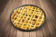 Domowej roboty jabłczany kulebiak z pieczenia naczyniem na stole Zdjęcia Stock
