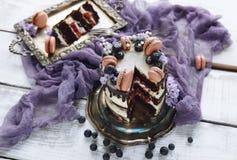 Domowej roboty kawy i wanilii tort z czekoladowym mrożeniem, dekorującym z czarną jagodą, macaroons i kwiatami, Fotografia Stock