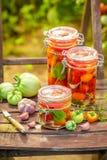 Domowej roboty kiszeni pomidory na starym krześle w szklarni fotografia stock