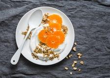 Domowej roboty kokosowy jogurt z granola i tangerines na popielatym tle Gluten uwalnia zdjęcia stock
