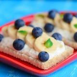 Domowej roboty kremowego sera kanapki Zdrowy skorupiasty chleb ściska z serową śmietanką, bananami i jagodami na czerwień talerzu Obraz Royalty Free
