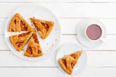 Domowej roboty kulebiak z jab?kami, cynamon i fili?anka herbata na bia?ym drewnianym stole zdjęcie stock