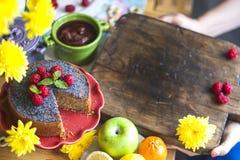 Domowej roboty kulebiak z makowymi ziarnami i malinkami Wyśmienicie śniadanie na kolorze żółtym i stole kwitnie Odgórny widok kos zdjęcie stock