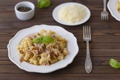 Domowej roboty makaronu carbonara włoszczyzna z bekonem, jajka, Parmezański ser na bielu talerzu na ciemnym tle fotografia royalty free