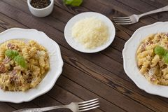 Domowej roboty makaronu carbonara włoszczyzna z bekonem, jajka, Parmezański ser na bielu talerzu na ciemnym tle obraz stock