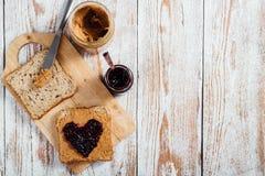 Domowej roboty masło orzechowe i galareta ściskamy na drewnianym tle Zdjęcie Royalty Free