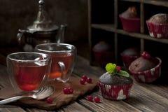 Domowej roboty muffins z czarnymi jagodami i filiżanką herbata na rocznika drewnianym tle Zdjęcie Stock