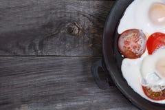 domowej roboty omelette w rocznika frypan z pomidorami na nieociosanym drewnianym tle, odgórny widok, bezpłatnej przestrzeni teks Zdjęcie Royalty Free