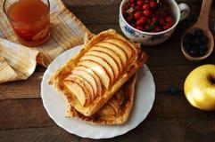 Domowej roboty organicznie rumiani kulebiaki z jabłka ptysiowym ciastem, przygotowywającym jeść Wyśmienicie jabłka chuch na drewn Fotografia Stock