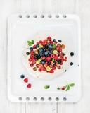 Domowej roboty Pavlova tort z świeżymi ogrodowymi jagodami na białej wypiekowej tacy nad lekkim drewnianym tłem Obraz Royalty Free