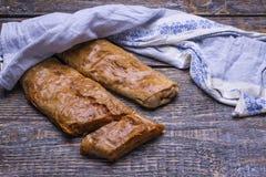 Domowej roboty pieczenie - strudle z mięsem i kapustą na drewnianej desce, tło Zdjęcia Stock
