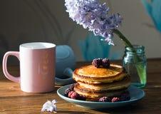 Domowej roboty puszyści bliny z świeżymi jagodami na błękitnym talerzu na drewnianym stole Zdjęcia Royalty Free
