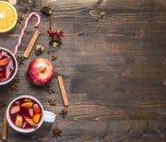Domowej roboty rozmyślający wino z jabłkiem, pomarańcze, cynamon, cloves i inni składniki, kłaść out wokoło na drewnianym nieocio Zdjęcie Stock