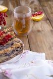 Domowej roboty słodki kulebiak dla śniadania z cytryną i jagodami czarny rodzynek i czerwony rodzynek szklana herbata brązowe dre Obrazy Stock