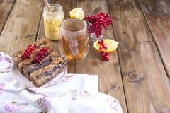 Domowej roboty słodki kulebiak dla śniadania z cytryną i jagodami czarny rodzynek i czerwony rodzynek szklana herbata brązowe dre obrazy royalty free