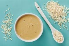 Domowej roboty tahini lub tahina, pasta od zmielonych sezamowych ziaren na błękitnej rocznik powierzchni Obraz Stock