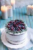Domowej roboty tort dekorował jagody na talerzu nad drewnianym turkusowym tłem Zdjęcie Stock