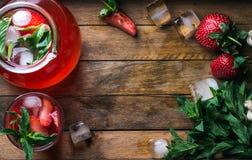 Domowej roboty truskawki mennicy lemoniada słuzyć z świeżymi jagodami i lodem nad drewnianym tłem, odgórny widok, kopii przestrze Zdjęcia Royalty Free