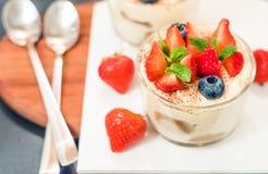 Domowej roboty włoski deserowy tiramisu z strawberrie, czarna jagoda, mennica w szklanych słojach, odgórny widok na białym tle fotografia stock